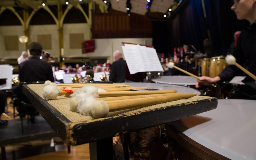 Timpani sticks on a traps table in front of a musician playing the timpanis. In the distance you can see an orchestra.