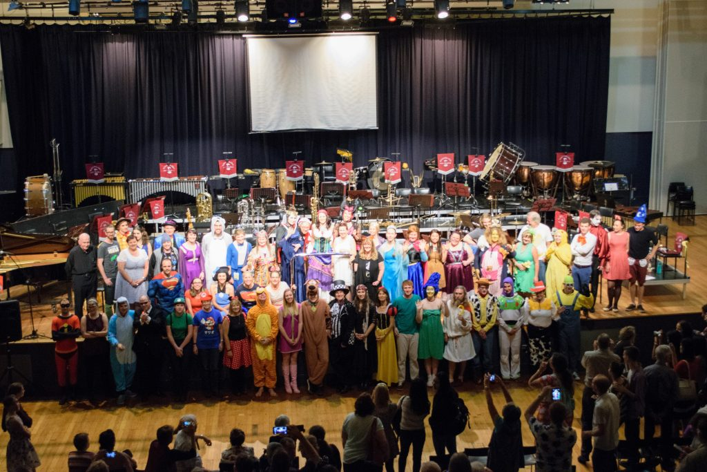 The Musicians of QWAB stand at the front of a stage dressed up as characters from Animation