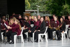 Queensland Wind and Brass sit in orchestra formation on a stage in Roma Street Parklands
